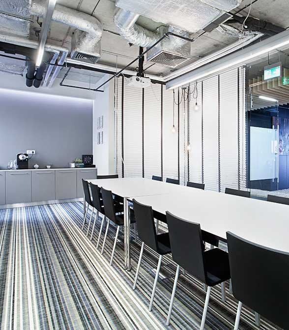 Blue, white and grey striped woven vinyl flooring in the office of Rohlig Suus in Warsaw, Poland