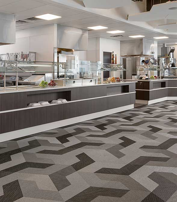 Grey Bolon Studio Wing tiles creating a modern flooring pattern with 3D effects in the New Era Field football stadium in Buffalo, New York